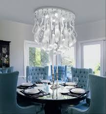 modern artistic dining room crystal chandelier over black round pedestal dining table and blue wingback