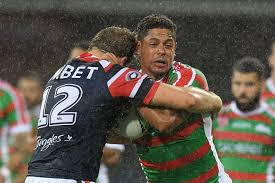 dane gagai holds the ball in the rain as he tries to beat the defence