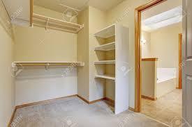 empty walk in closet. Bright Empty Walk-in Closet With Wood Shelves, Beige Carpet Floor. Stock Photo Walk In