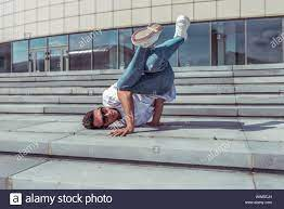 Young stylish man on steps, guy a dancer, in summer in city, dancing break  dance, healthy fitness athlete life style, white t-shirt, jeans, sneakers  Stock Photo - Alamy
