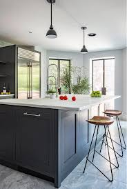 dark gray kitchen island with honed white marble countertop and wood and iron stools