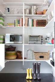 fantastic walk in pantry boasts stacked wraparound shelves filled with small appliances over a dark stained wood floor
