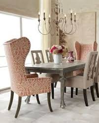 love the french chandelier and the wing chairs haute house liday dining table benjamin carved back chair and pink damask wing chair