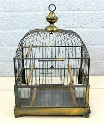 an antique bird cage with feeder bowls brass glass porcelain