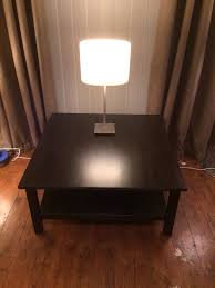 black brown ikea hemnes coffee table topped with high gloss black glass
