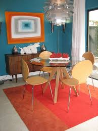 rug and wall art bring orange into this midcentury dining room on orange and