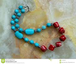 a closeup of a handmade gemstone jewelry made with turquoise pewter and big red c beads