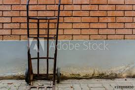sack truck against old brick wall