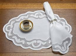 lovely design of placemats showing oval white fabric placemats with carving motif on the table