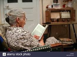 old lady reading book sitting in an arm chair with an old radio set in the background