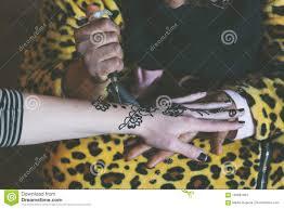 мусульманская женщина делает временную татуировку хны на белой