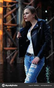a beautiful girl in a black leather jacket a white t shirt and blue jeans stands on an industrial background shooting in daylight selective sharpness