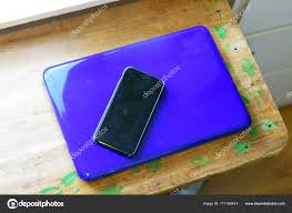 Turned Off Cell Phone On Top Of Closed Laptop Stock Photo
