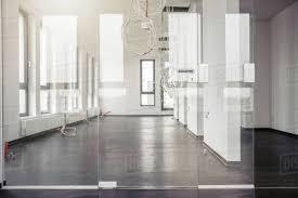 office corridor door glass. Glass Door In Front Of Power Cables Hanging From New Office Corridor Ceiling