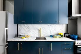 the marble countertops and backsplash gold hardware crystal knobs and rich blue cabinetry make for a classy and timeless kitchen