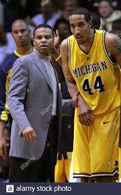 University of Michigan head coach Tommy Amaker (L) and center Courtney Sims  watch from the bench as Michigan takes the lead over Michigan State during  the second half of their NCAA game