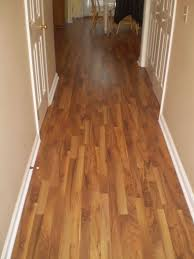 bamboo laminate flooring matched with tan wall with white baseboard molding for home interior idea