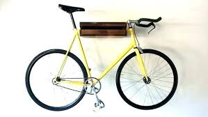 a green bicycle locked to u shaped outdoor bike rack is missing its seat diy how