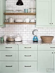 light green painted kitchen cabinets with shiny white subway tile backsplash