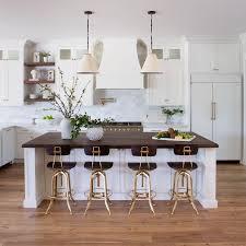 dark butcher block island countertop with brown wood stools