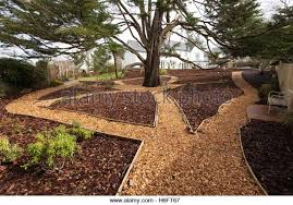 garden bark. Wood Chippings Laid As Garden Paths, Wooden Edging, And Bark Used Mulch