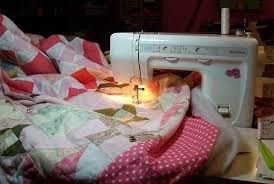 How to Baste a Quilt with Safety Pins & A Pin Basted Quilt Being Quilted Adamdwight.com