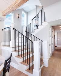 Clean modern iron black railing Iron stair rails with white oak wood floors  and overhead beams create a drool-worthy staircase!