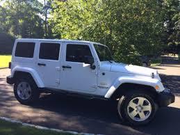 white jeep wrangler unlimited sahara 4 door 4 wheel drive navigation