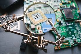 desktop with broken disassembled laptop electronic parts of pc motherboard microprocessor ysis computer cpu through magnifying glass