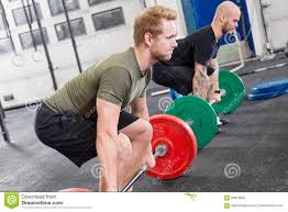 two dedicated men trains deadlift at fitness gym center