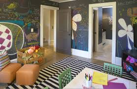 fun playroom with white black striped ikea stockholm rand rug black chalkboard paint orange ottomans white desk green chairs and woven toy bin
