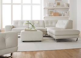 simple modern minimalist living room decoration with white leather sectional sofa with chaise and ottoman plus small wall mounted bookshelf in the corner