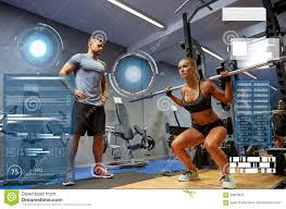 Man And Woman With Bar Flexing Muscles In Gym Stock Image