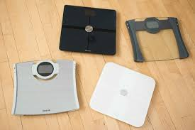 four bathroom scales one black one glass one silver and one