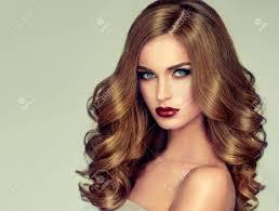 膨大な髪の若い茶色の髪の女性長く密な巻き毛の髪型と鮮やかな