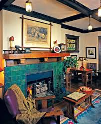 stunning green tile accented by riveted iron straps makes the fireplace the centerpiece of the room