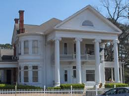 Greek Revival style architecture- house with pillars holding an over  hanging roof containing a balcony underneath.