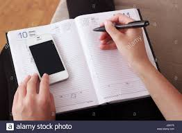 Agenda Business Woman Writing Contact List From Mobile Phone Into Her