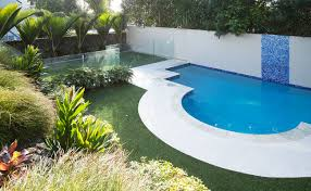 half circle pool with landscaped gardens surrounding it