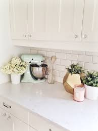 shaker cabinets paired with white quartz countertops and subway tiled backsplash alongside mint green pistachio kitchenaid mixer and gold faceted vase