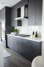 dark gray flat front kitchen cabinets with gray mosaic tile backsplash