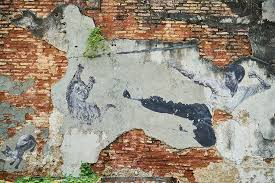 bruce lee kicking mural on brick wall