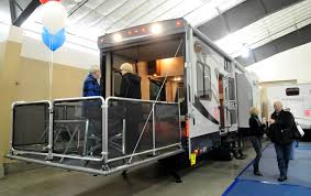 pers walk around a giant toy hauler rv with a rear r that doubles as a