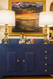 a cobalt cabinet serves as a bar a landscape painting by andrea gomez hangs above