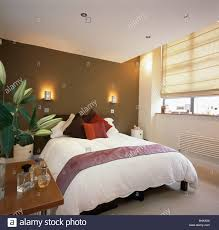 Light Brown And White Bedroom Wall Lights On Brown Wall Above Bed With White Duvet In