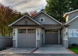 one of two attached garages both with taupe garage doors is extended so that