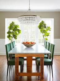 in this dining room white wainscoting extends up the wall and is topped with gray grcloth wallpaper around a large window inviting plenty of natural