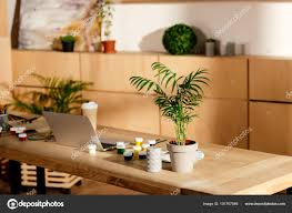 interior artist studio painting supplies laptop potted plant wooden table stock photo