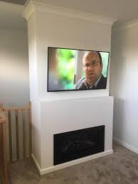 tv mounted on wall above fireplace by jim s antennas