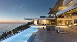 patio with pool. Illuminated Modern, Luxury Home Showcase Exterior Patio With Lap Pool And  Ocean View At Twilight